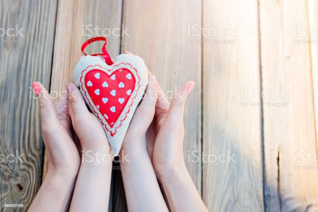 Child and mother holding heart in hands over a wooden table. Mothers...