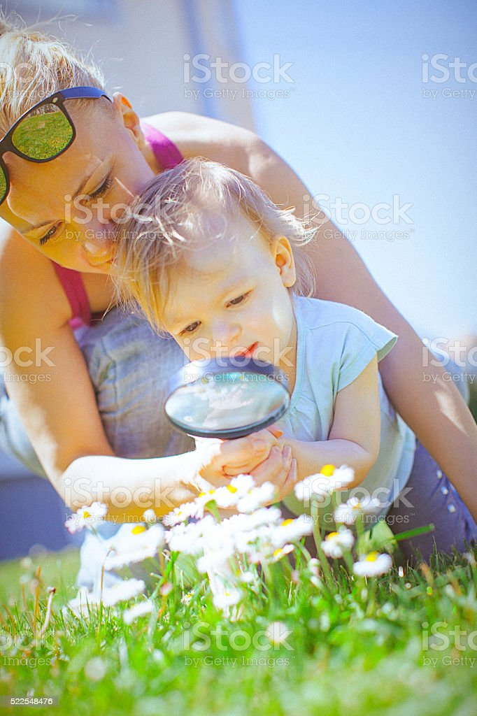 Child and mother looking flower through magnifying glass. stock photo