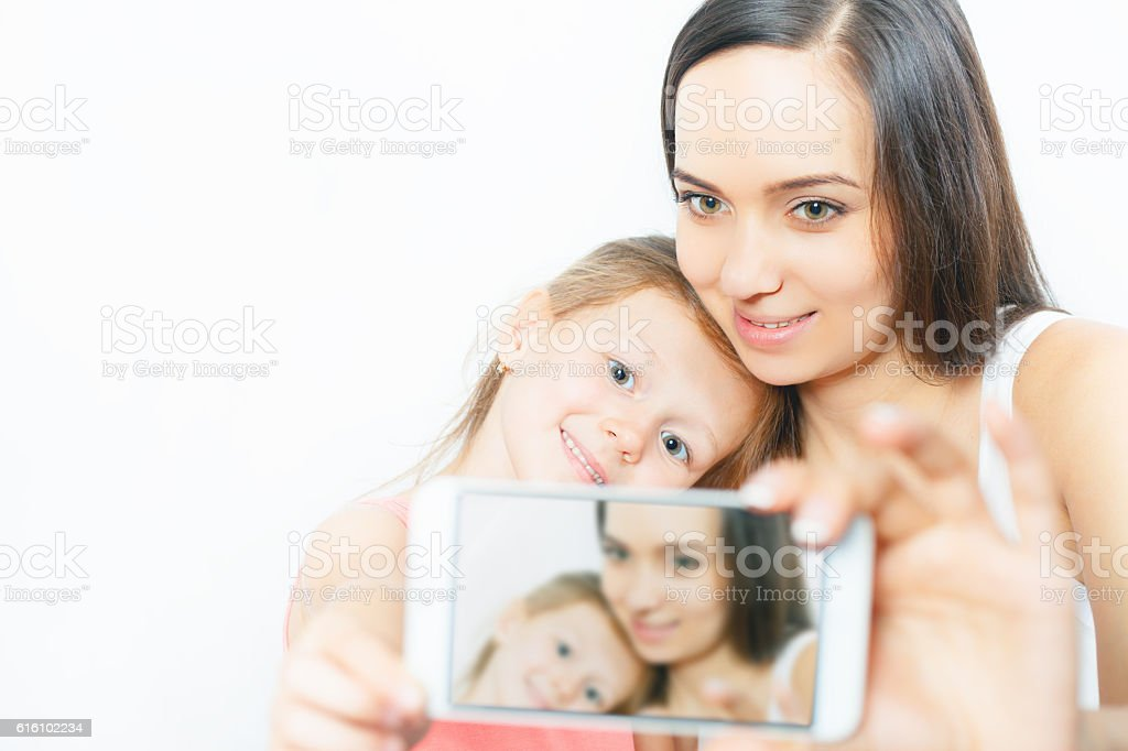 Child and mother make selfie on mobile phone, good camera stock photo