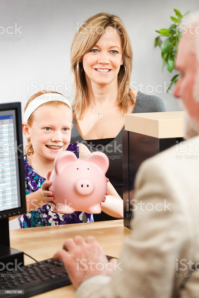 Child and Parent Taking Saving to Retail Bank Teller Counter stock photo