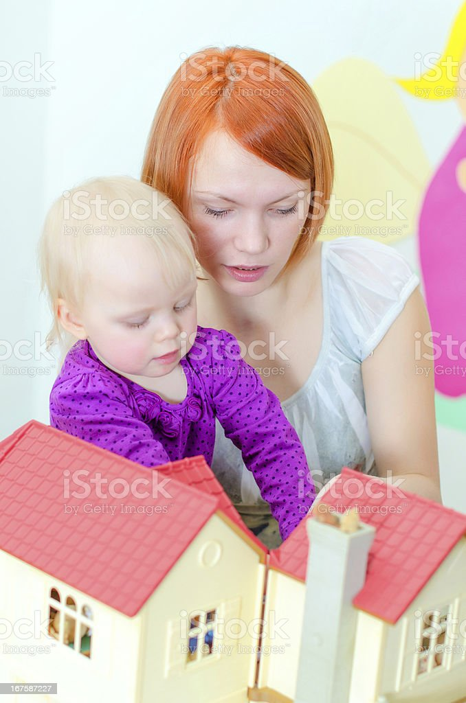 Child and their mother playing with dollhouse royalty-free stock photo