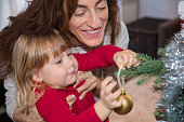 child and woman placing ball in christmas tree