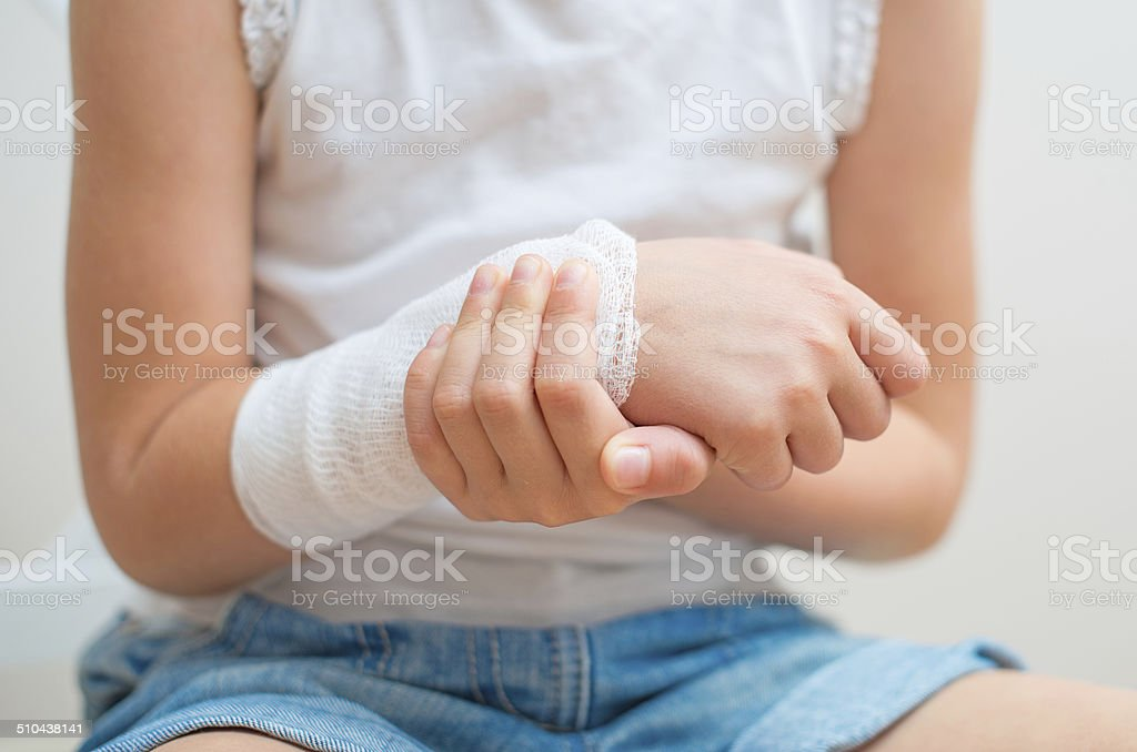 Child arm with gauze bandage on it. stock photo