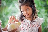 Child asian little girl putting coin into Piggy Bank