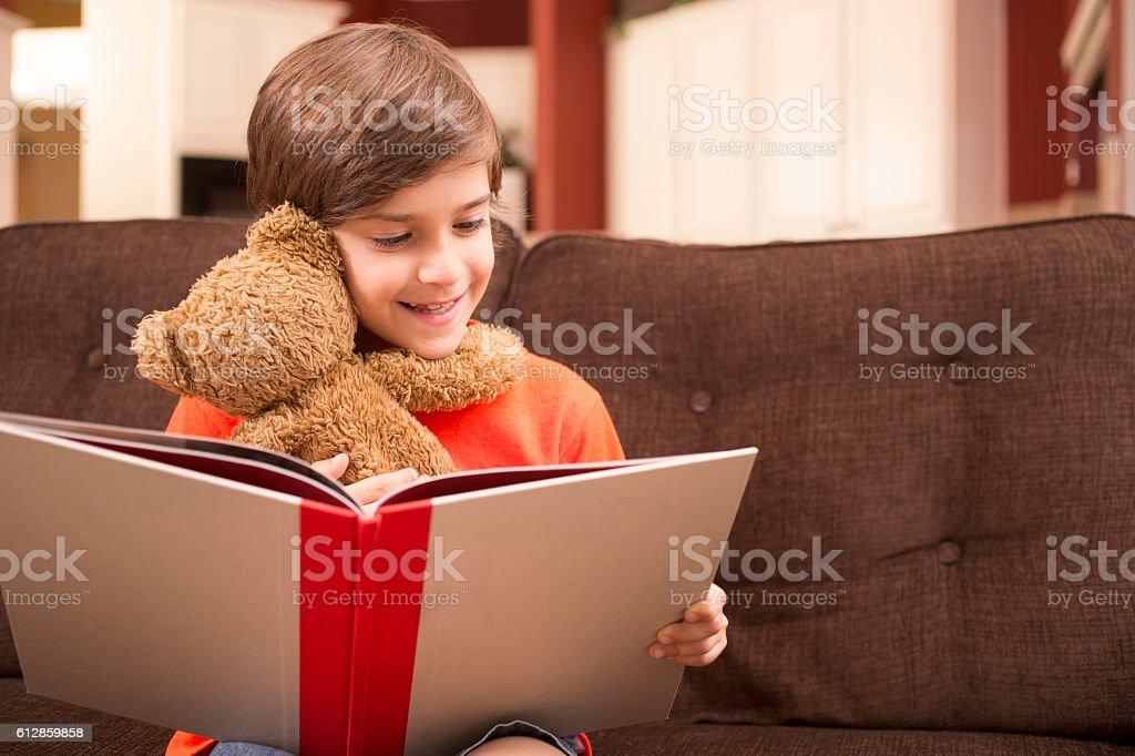 Child at home reading book with teddy bear. stock photo