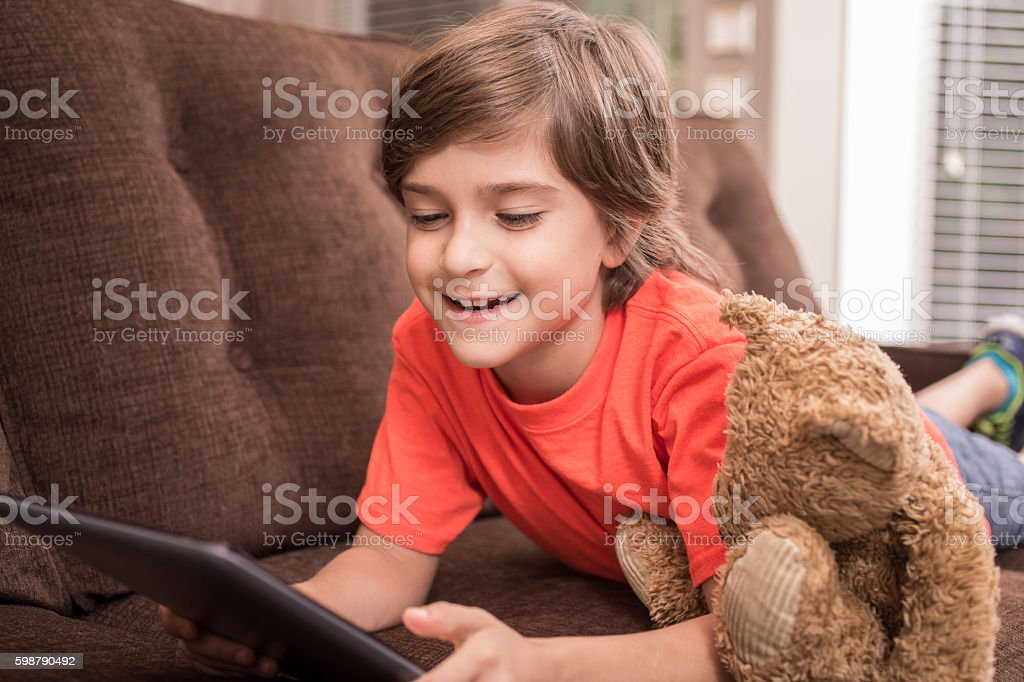 Child at home reading digital tablet with teddy bear. stock photo