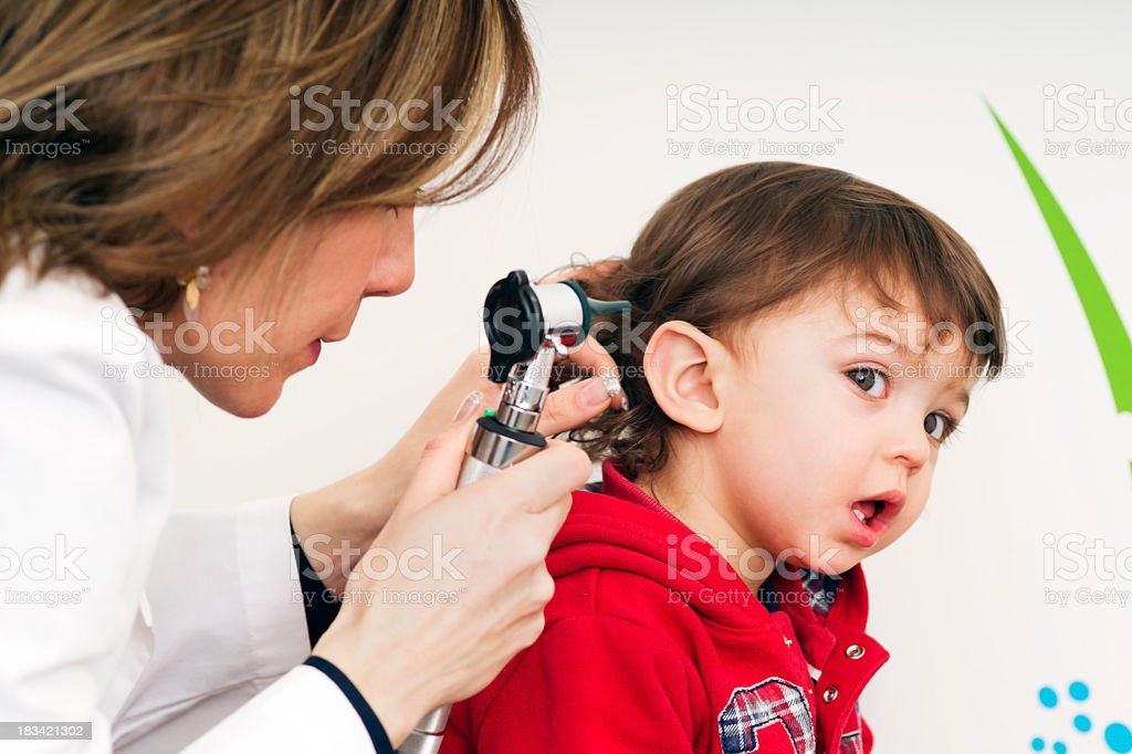 A child at the doctors office receiving a ear exam stock photo
