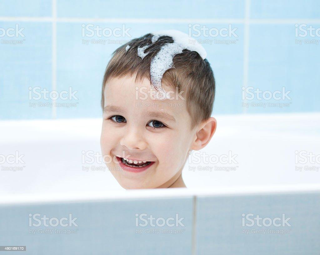 Child bathes in a bathroom stock photo