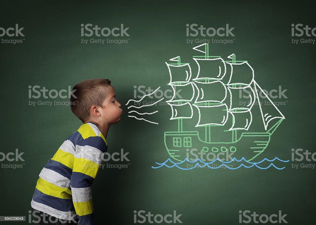 Child blowing a chalk sailboat stock photo