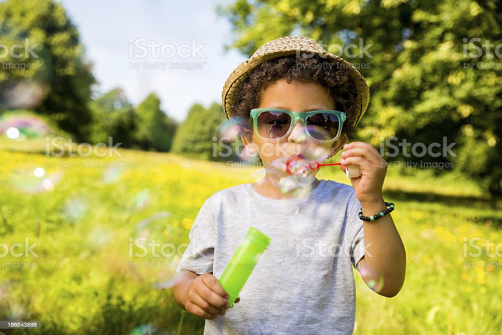 Child blowing bubbles in park royalty-free stock photo