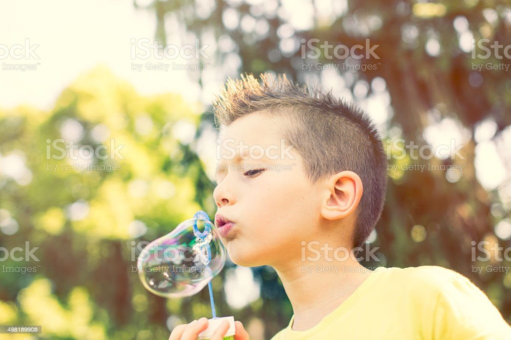Child blows soap babbles in te park stock photo