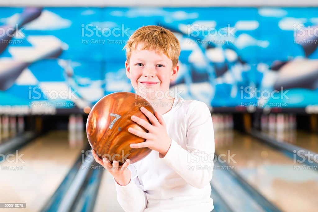 Child bowling with ball in alley stock photo