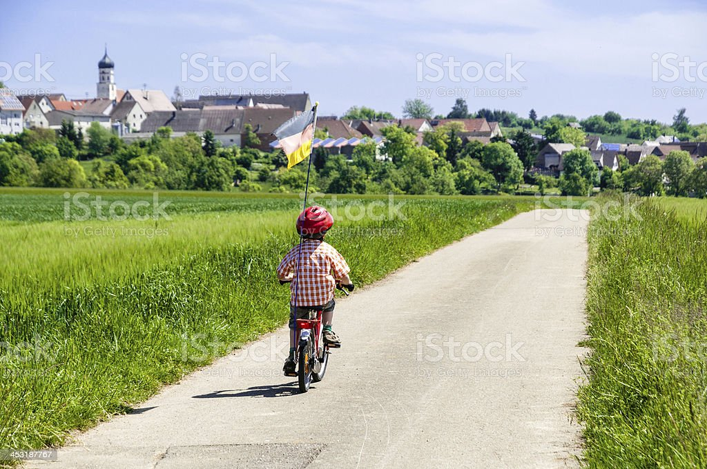 Child, boy, from behind in a rural landscape by bike stock photo