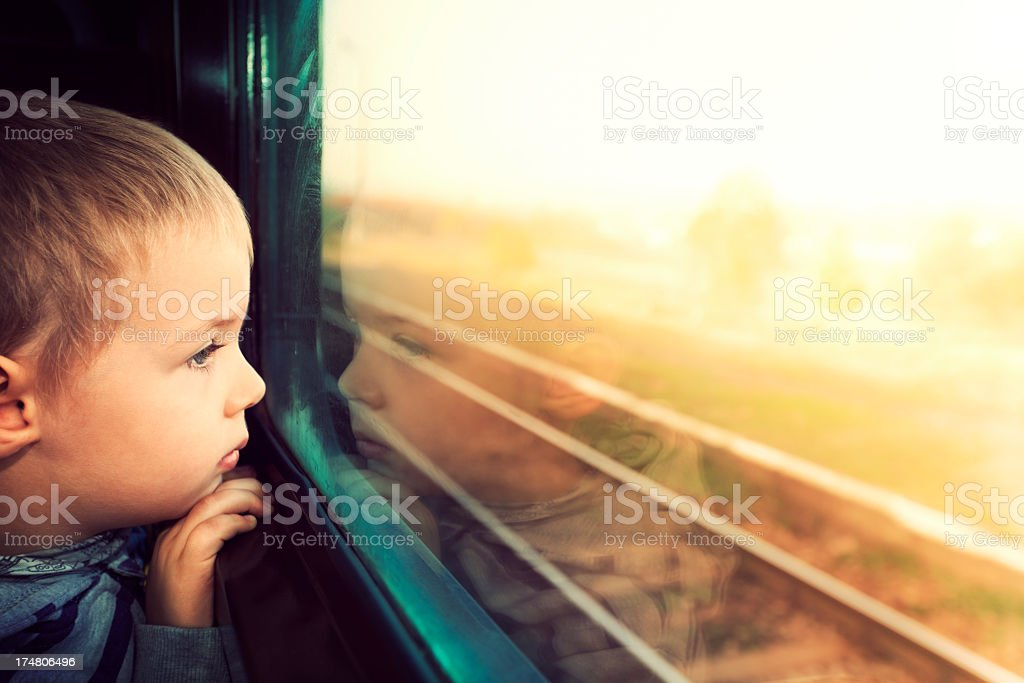 Child boy looking out of a window train stock photo