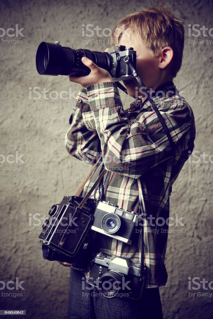 Child blond boy photographer with many cameras around his neck with...