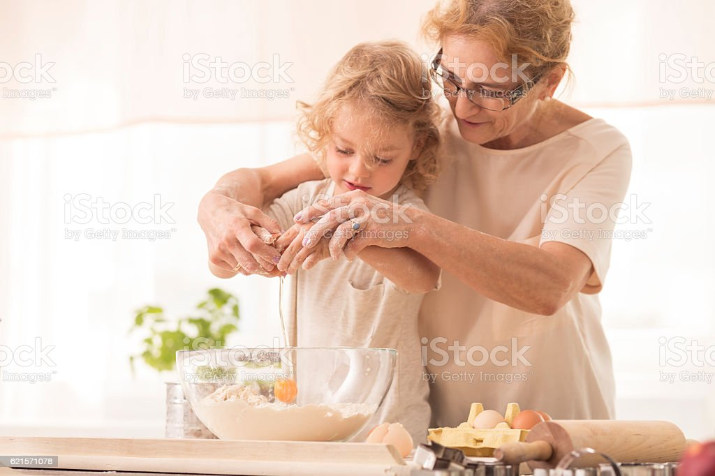 Child breaking the egg into a bowl stock photo