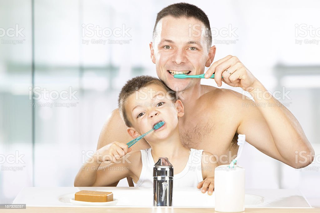 child brushes his teeth with dad royalty-free stock photo