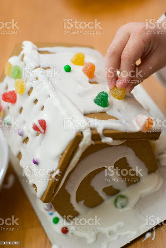 Child building gingerbread house royalty-free stock photo