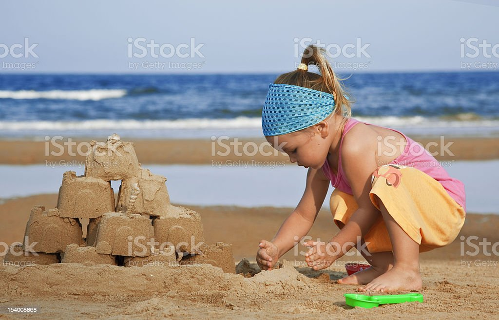 Child builds a sand castle on the beach royalty-free stock photo
