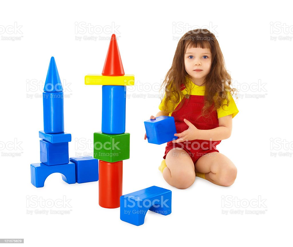 Child builds a toy castle on floor royalty-free stock photo
