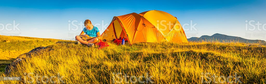 Child camping in idyllic mountain meadow summer sunset panorama Scotland stock photo