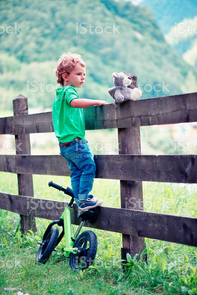 Child climbed on the wooden fence stock photo