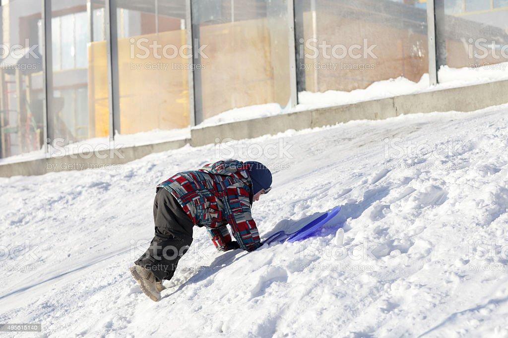 Child climbing on a snowy hill stock photo