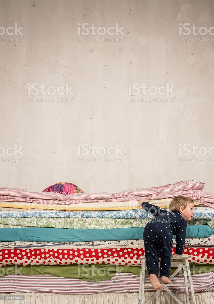 Child climbs on the bed - Princess and the Pea. stock photo