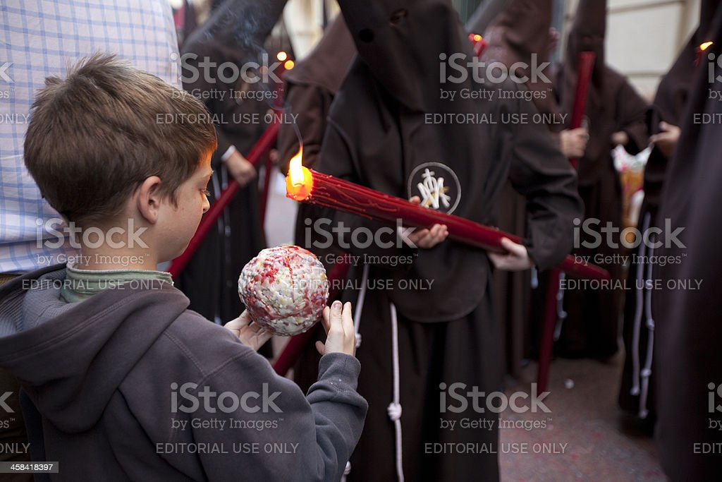 Child collecting the wax dripping from candles royalty-free stock photo