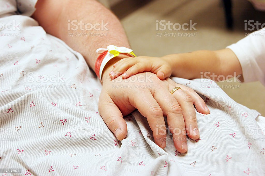 Child comforting sick parent on hospital bed stock photo