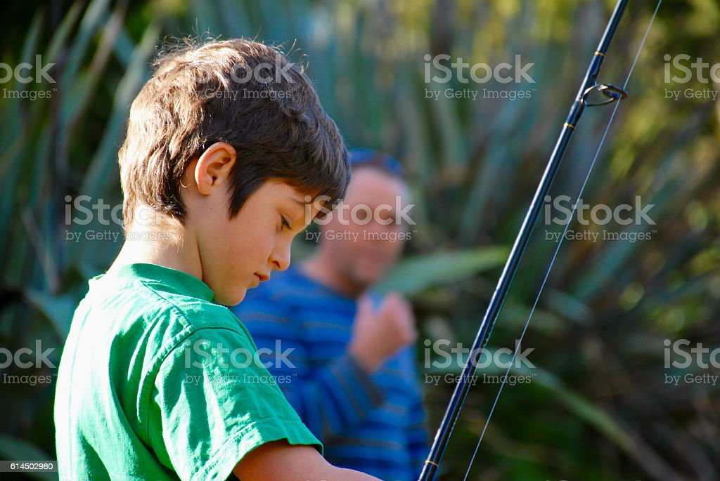 Child concentrating  on his Fishing Rod stock photo