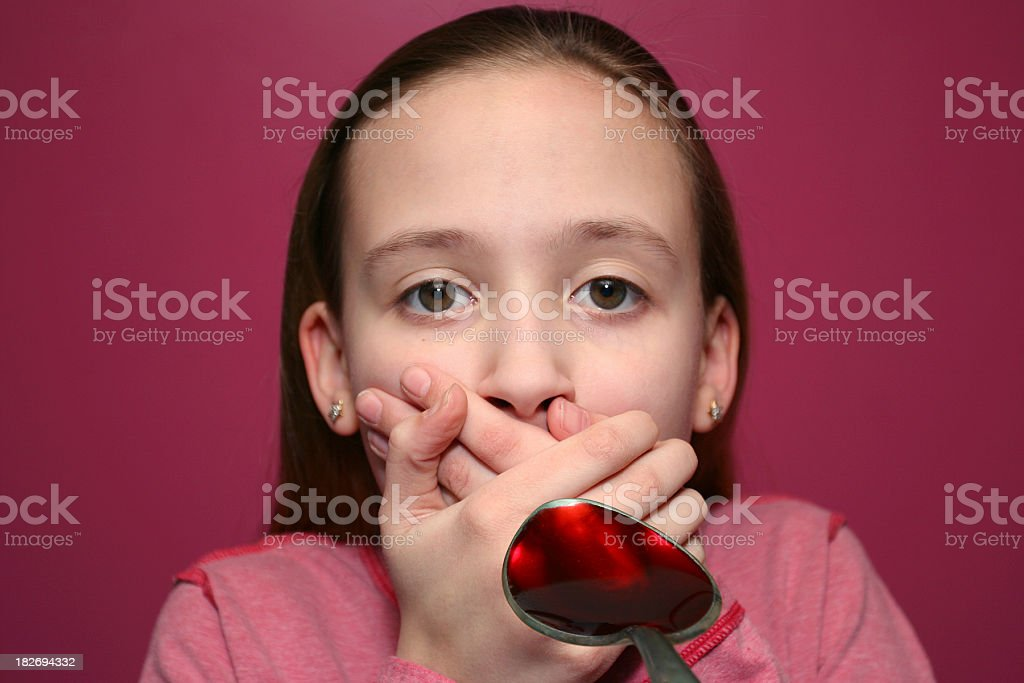 Child covering mouth when shown spoonful of cough syrup stock photo
