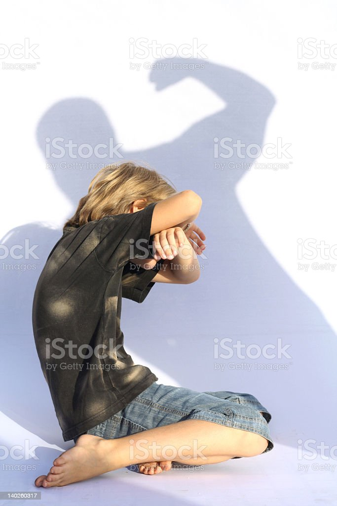 Child cowering from a man's shadow stock photo