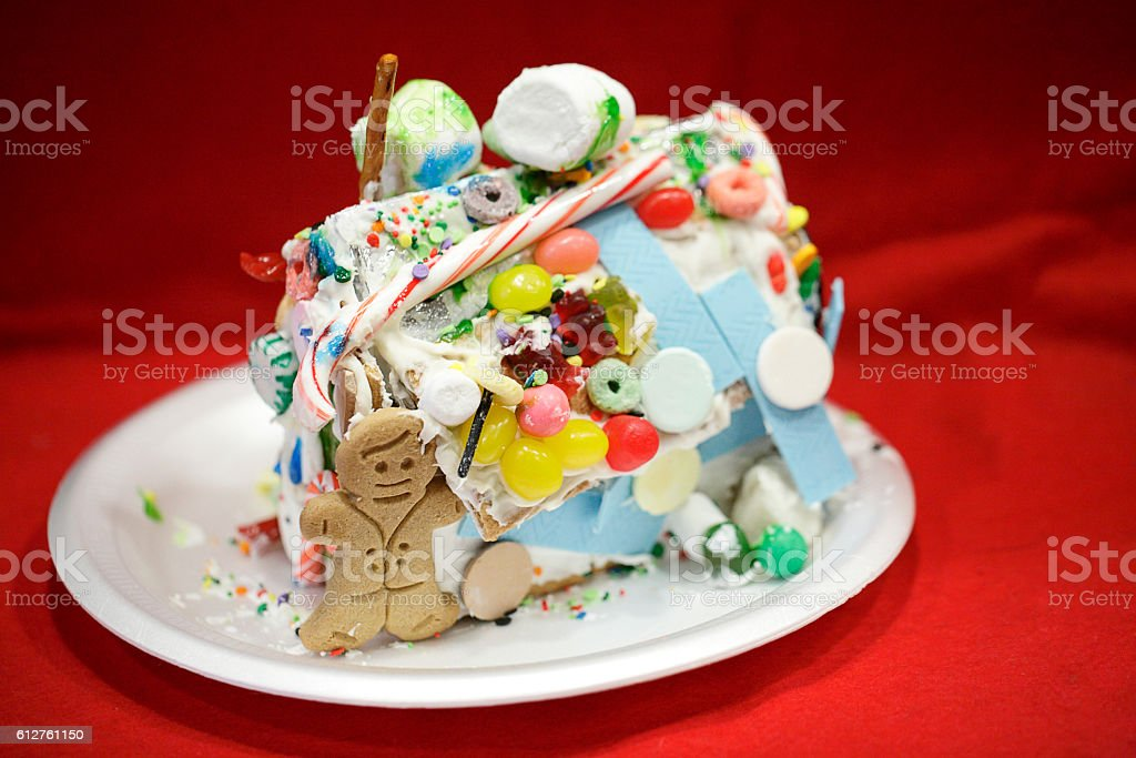 Child crafted and original gingerbread house against red background stock photo