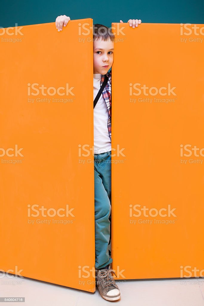 child curiously peeks out the door stock photo