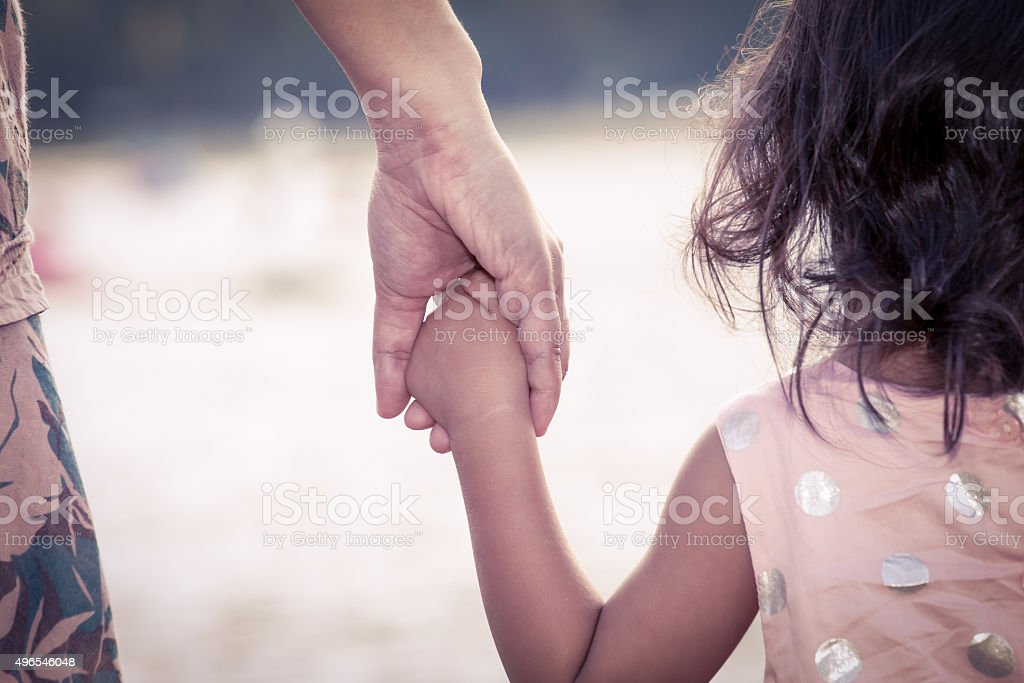 child cute little girl and mother holding hand together with love in...