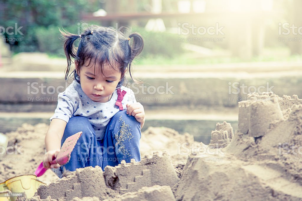 Child cute little girl playing with sand in playground stock photo