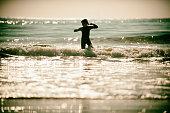 Child dancing in the ocean