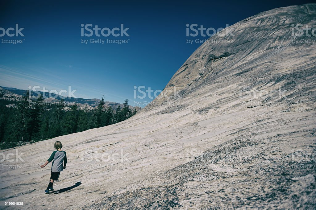 Child dancing on a mountain in Tuolumne Meadows, California stock photo