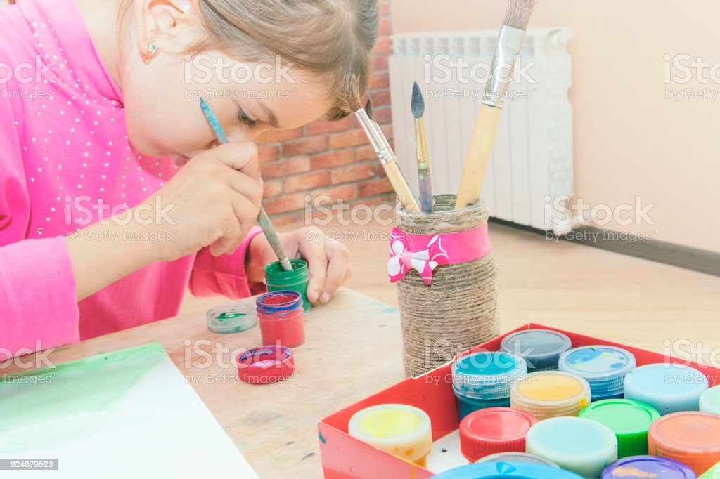 child dips a finger in paint what to draw stock photo