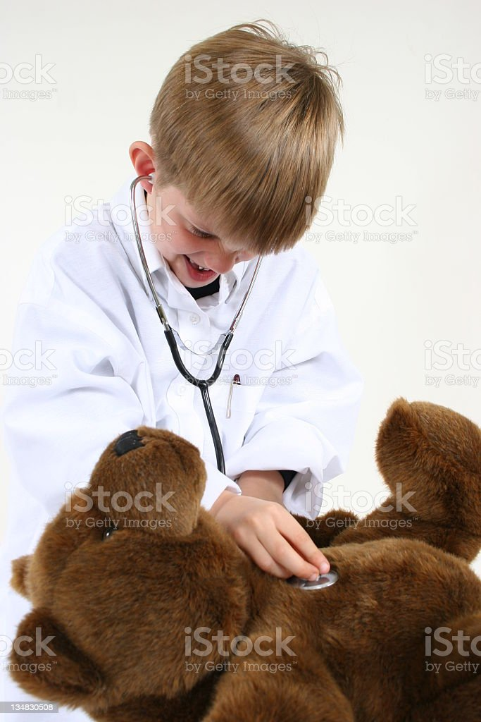 Child doctoring bear. royalty-free stock photo