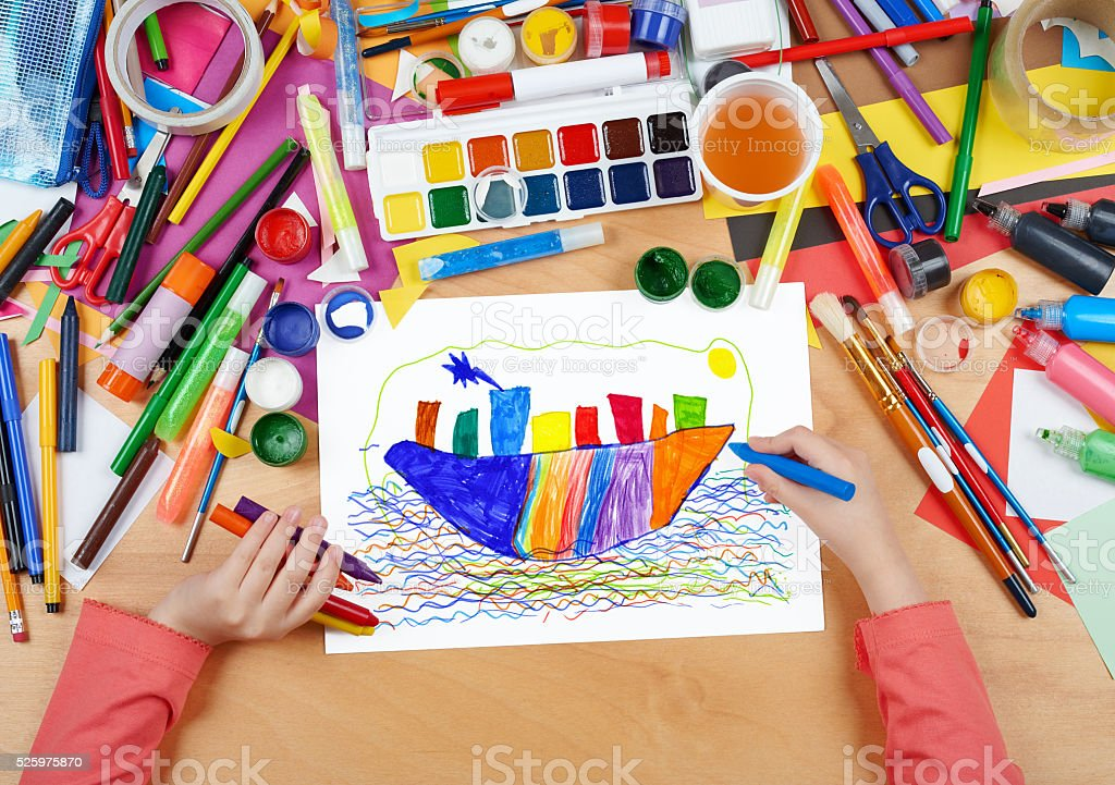 child drawing ocean liner ship, top view hands stock photo