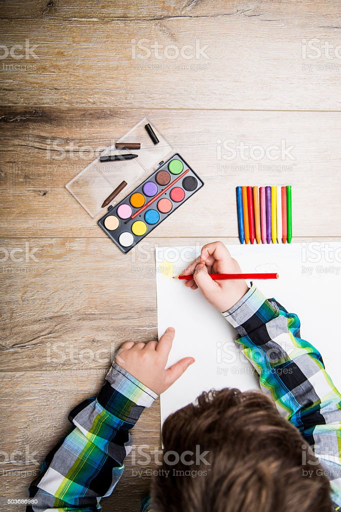 Child drawing on a white paper stock photo