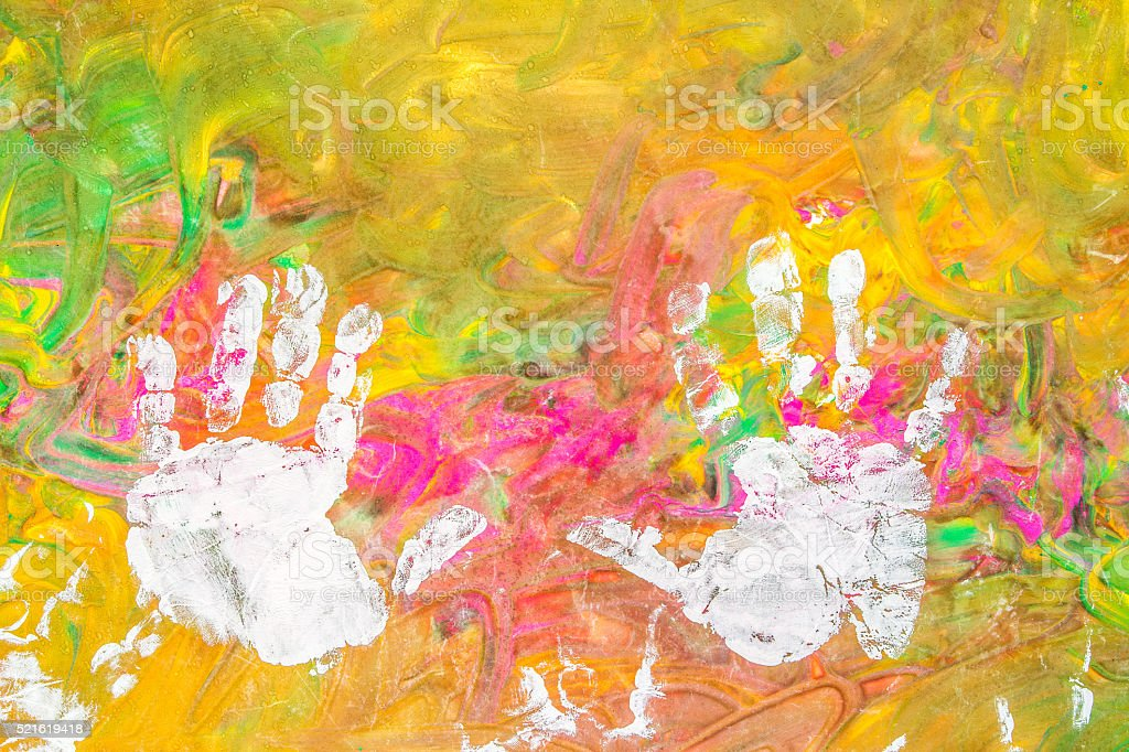 Child drawing painting with his white hands on colorful background stock photo