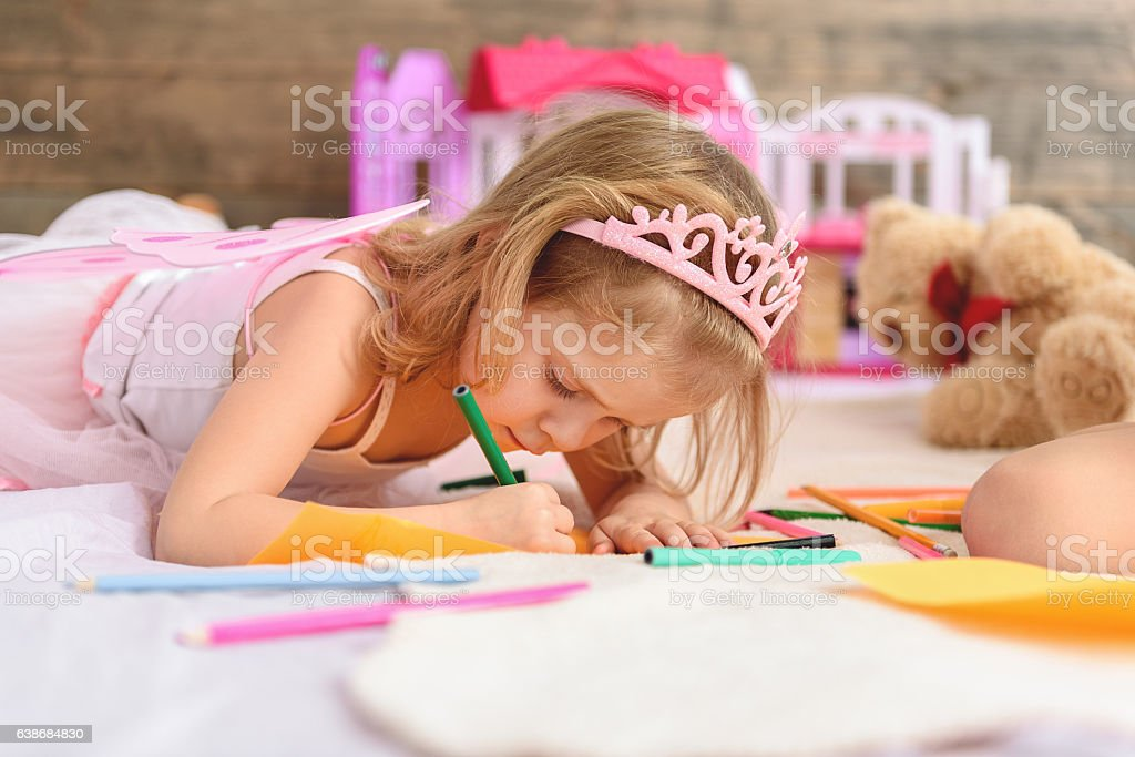 Child drawing pictures in bedroom stock photo