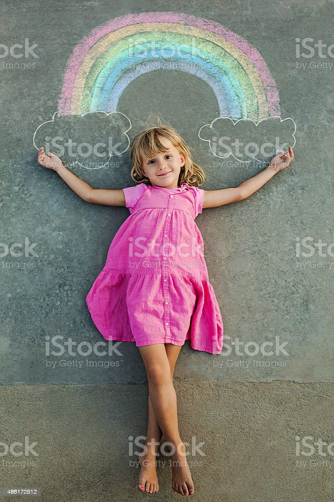 Child drawing rainbow with chalk stock photo