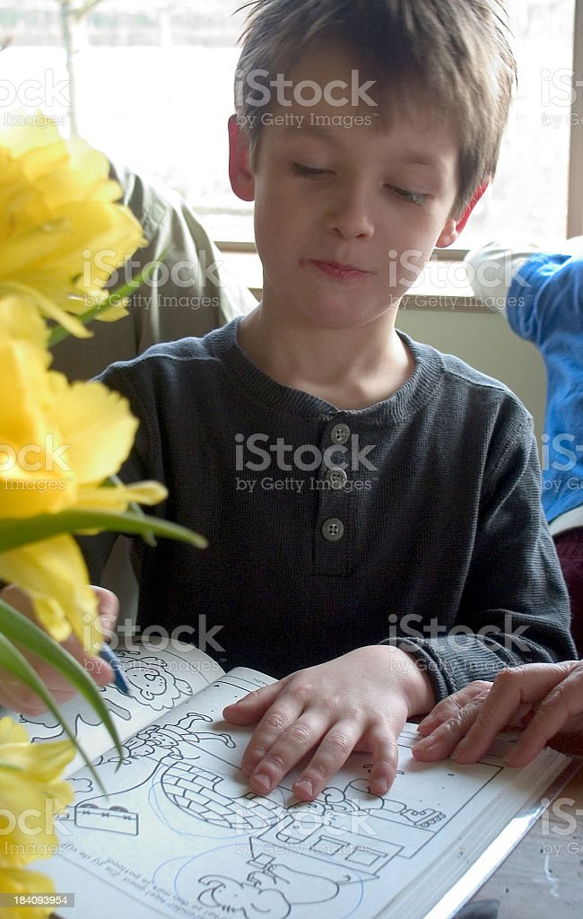 Child drawing with daffodils and book stock photo
