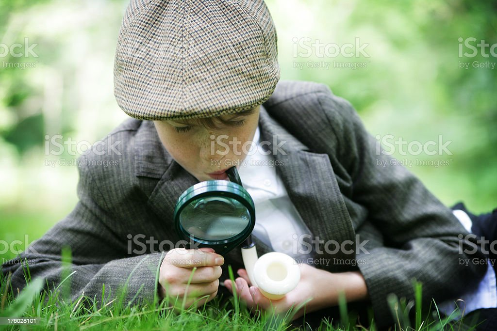 Child Dressed as Sherlock Holmes Uses Magnifying Glass in Nature stock photo