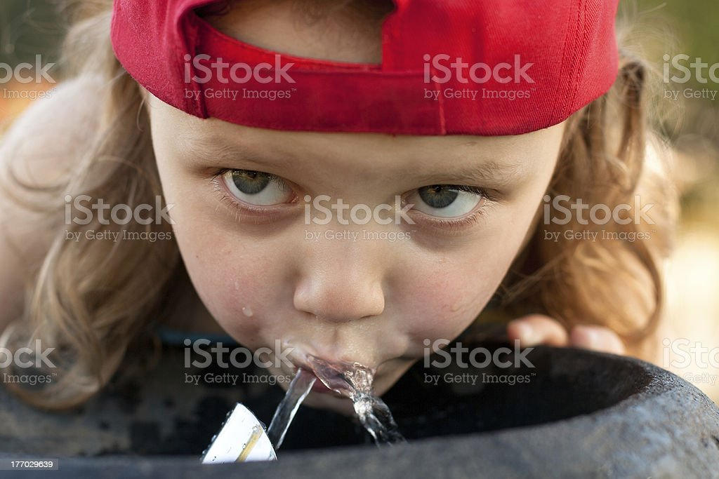 child drinking from water fountain stock photo
