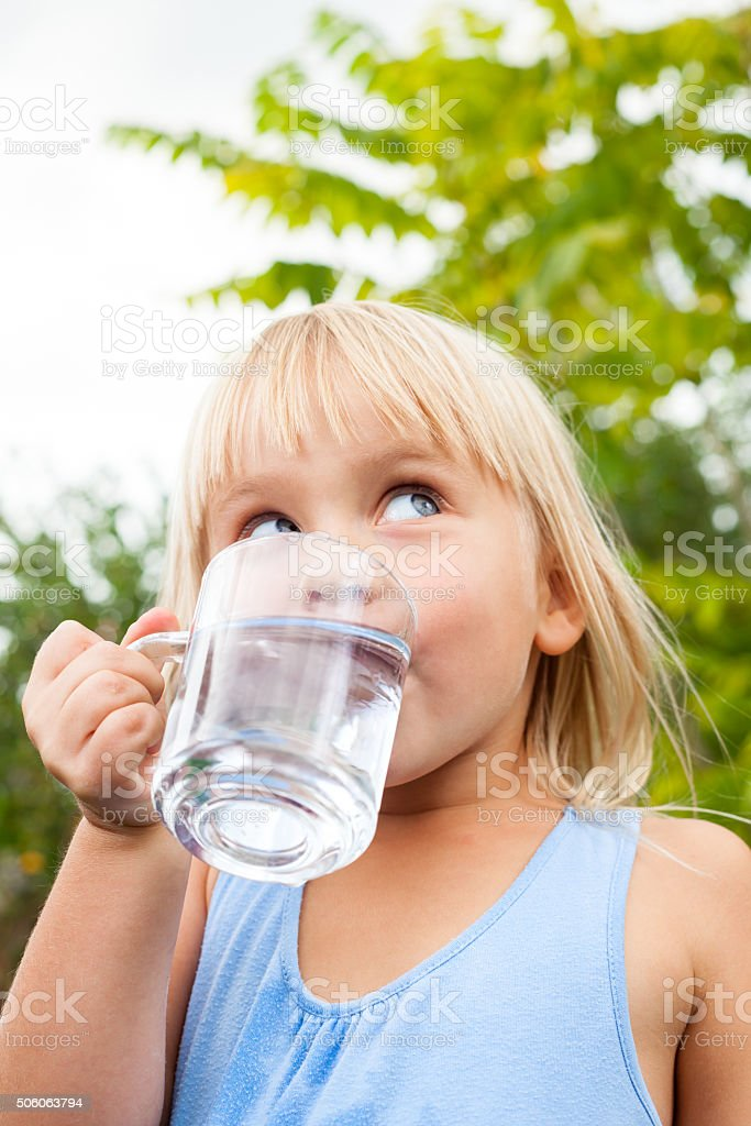 Child drinking water outdoors stock photo